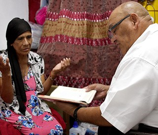 Chaplain Cristiano Artigas visits patient Maria Estrada Hernandez at her west Phoenix home