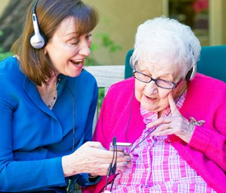 Maribeth Gallagher enjoying music with patient Sue Crawford at Gardiner Home