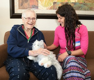 "Social worker Michelle Bales visits with patient Walter ""Wally"" Brown and his mechanical cat, Sweetheart."