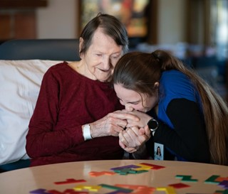 Caregiver kissing hand of dementia patient